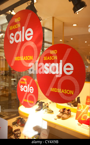 sale signs advertising low prices in shoe retail store - Stock Photo
