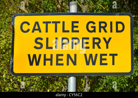 Slippery when wet warning sign on approach to Cattle Grid - Stock Photo