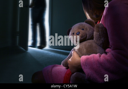Back view if a child in a dark room holding a teddy bear, a man has just left the room. - Stock Photo