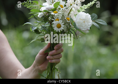 A woman's hand is holding a white flower bouquet freshly gathered from the garden during a summer rain. - Stock Photo