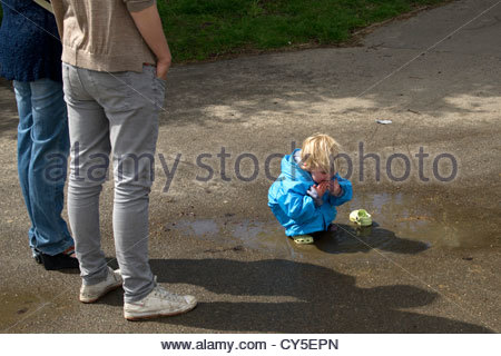 Children do like to play in puddles. Seen in a London park - Stock Photo