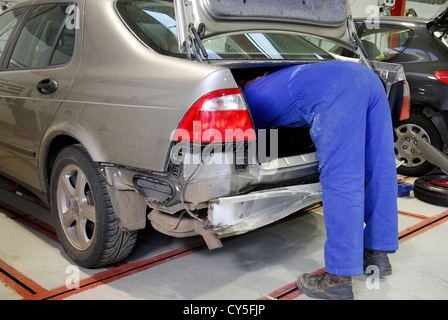 mechanic working inside car boot in garage - Stock Photo