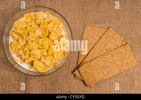 Bowl of cornflakes with milk and crispbreads on sacking background - Stock Photo