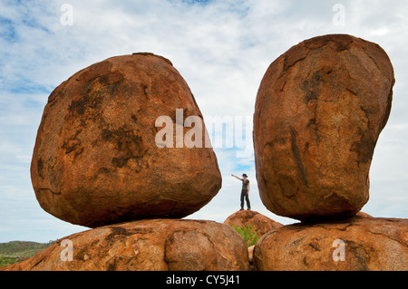 Person in the distance makes the Devils Marbles looking huge. - Stock Photo