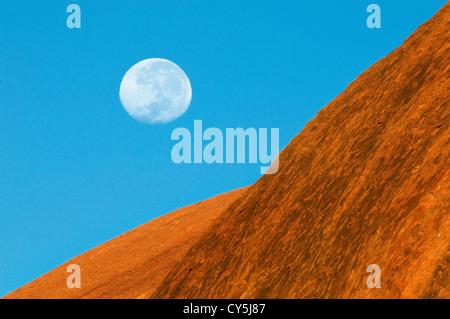 Moon is setting over Uluru's Rock Face. - Stock Photo