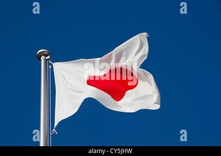 Japanese flag on flag pole against a blue sky - Stock Photo