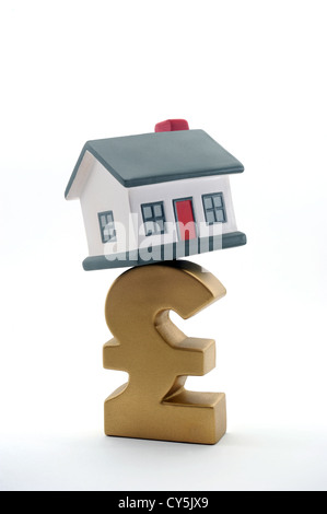 HOUSE BALANCING ON BRITISH POUND SIGN RE INTEREST RATES MORTGAGES INCOMES WAGES HOUSEHOLD COSTS BILLS MONEY CASH - Stock Photo