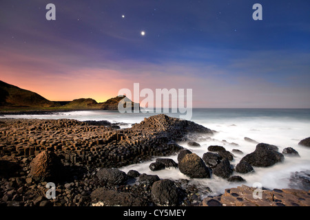 The Giants Causeway at night showing conjunction of Venus and Jupiter in sky. - Stock Photo