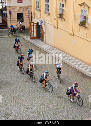 Prague bicycle tour group riding in Lesser Town (Mala Strana) near Charles Bridge - Stock Photo