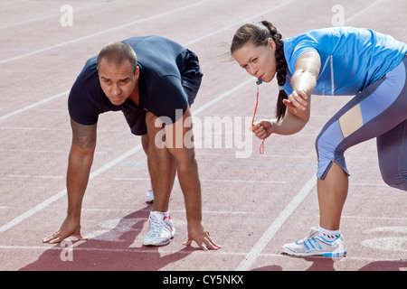 A woman in the stadium under starters orders from a man - Stock Photo