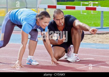 A man in the stadium on a sunny day under starters orders from a woman - Stock Photo