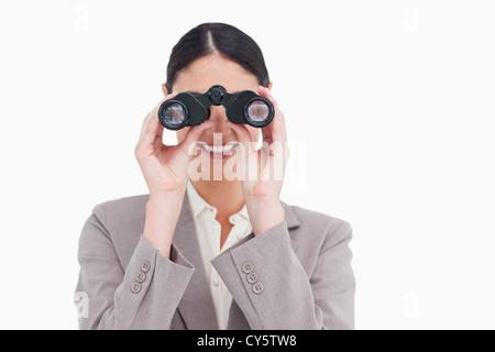 Smiling businesswoman looking through spy glasses - Stock Photo