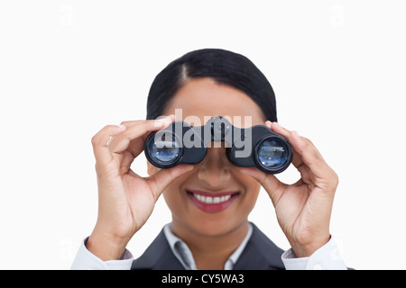 Close up of smiling saleswoman using spy glasses - Stock Photo
