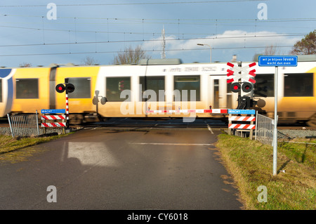 high speed train passing a secured railway crossing. The blue shield says 'If you want to stay alive, you better - Stock Photo
