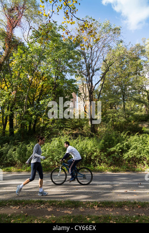 view of Central Park, Manhattan, New York City, with runner and cyclist using road for exercise - Stock Photo