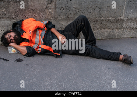 Homeless man sleeping on the streets of Paris. - Stock Photo