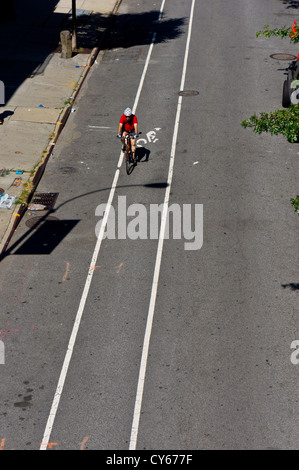 A lone cyclist pedals along a deserted stretch of road in downtown Manhattan, New York, seen from the High Line - Stock Photo
