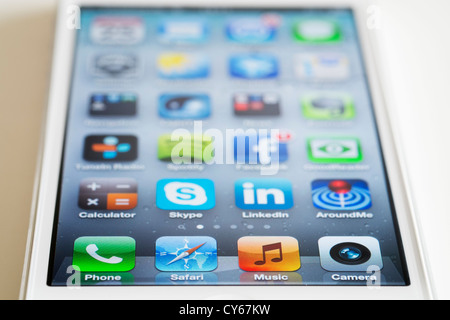 Close-up of new iPhone 5 smart phone showing screen with many apps - Stock Photo