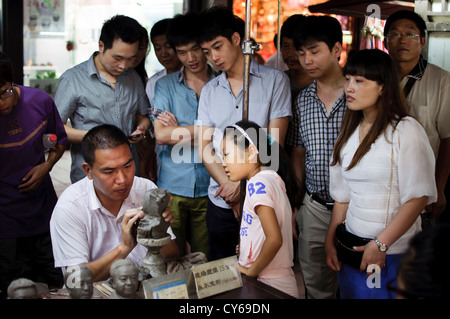 A man moulds a clay figure head on Qinghefang Old Street, Hangzhou, whilst bystanders look on - Stock Photo