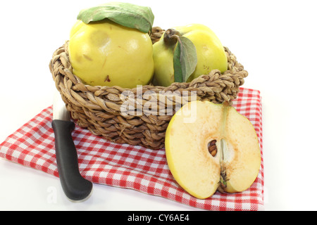 Quinces with leaves in a basket on a light background - Stock Photo
