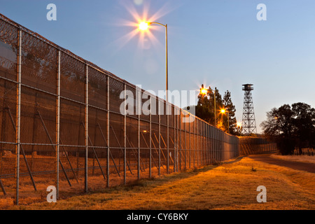 Prison security fence,  guard tower, before sunrise. - Stock Photo