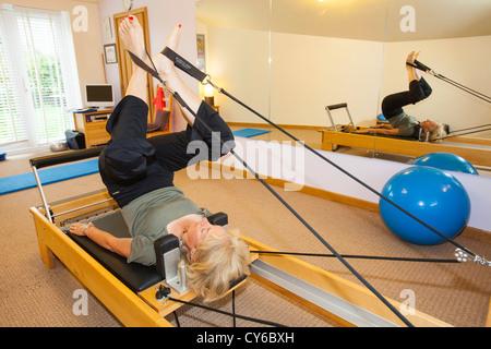 A Pilates instructor using a pilates reformer machine. - Stock Photo