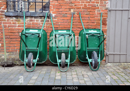 Three green wheelbarrows leaning against an outhouse wall - Stock Photo