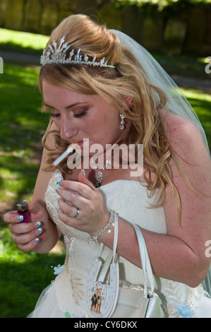 Model Released bride smoking a cigarette at the wedding - Stock Photo