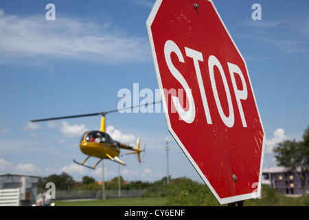 tourist light helicopter landing behind stop sign kissimmee florida usa - Stock Photo