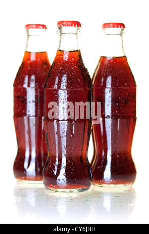 Three bottles of cold cola with water drops. Isolated on white - Stock Photo