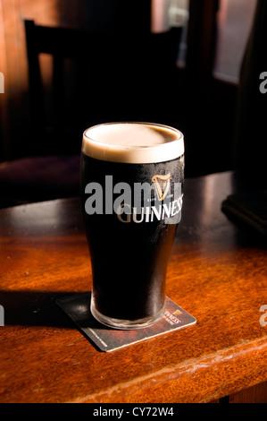 Pint of Irish Stout on a wooden bar - Stock Photo