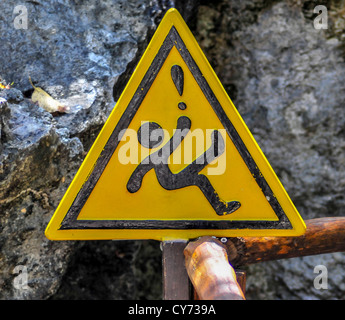 A yellow triangular slippery when wet warning sign in México Mexican with an ideogram of a falling figure triangle - Stock Photo