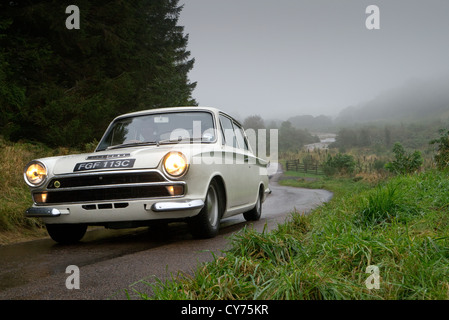 1965 Ford Lotus Cortina driving on a road in Northumberland UK - Stock Photo
