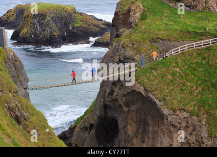 People walking on Carrick-a-Rede Rope Bridge from Carrick Island to the mainland in County Antrim, Northern Ireland, - Stock Photo