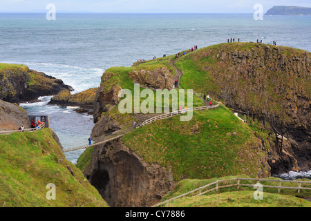 Tourists on Carrick Island with Carrick-a-Rede Rope Bridge on the north Causeway Coast in County Antrim, Northern - Stock Photo