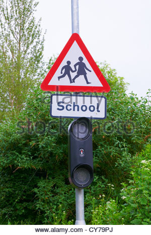 red and white triangular school children crossing warning road sign - Stock Photo