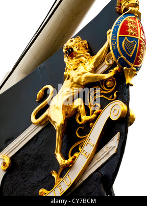 The British Coat of Arms with gilded lion on the bow of the hull of the SS Great Britain steamship designed by Brunel - Stock Photo
