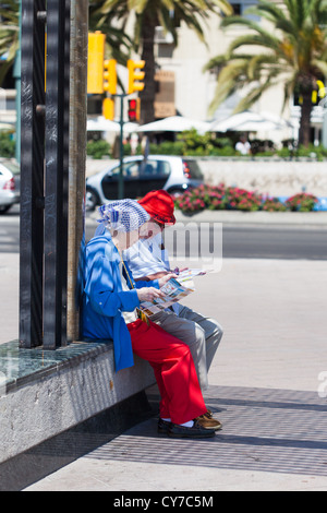 Two senior citizens studying tourist information. Malaga. Spain. Old couple looking at map. Malaga. - Stock Photo