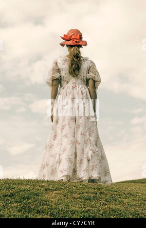 a woman in a flora dress and a red hat is running on a meadow - Stock Photo