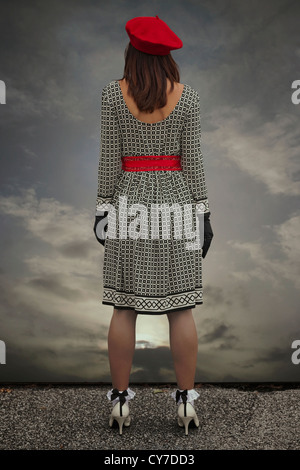 a woman in a black and white dress with a red cap is standing at the edge of a roof - Stock Photo