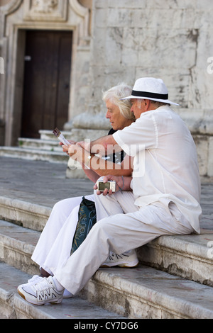 Two senior citizens studying tourist information. Cadiz. Spain - Stock Photo