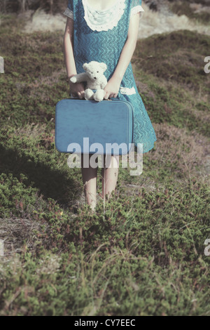 a young girl with a suitcase and a teddy bear - Stock Photo