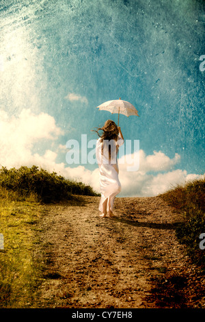 a girl in a white dress is walking in the dunes with a parasol - Stock Photo
