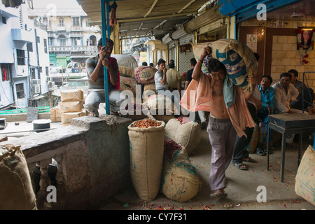 Porter carrying a large burlap sack on a verandah above an alley off Khari Baoli Road (Spice Market Bazaar off Chandni - Stock Photo