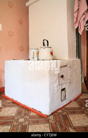 brick stove in rural wooden house - Stock Photo