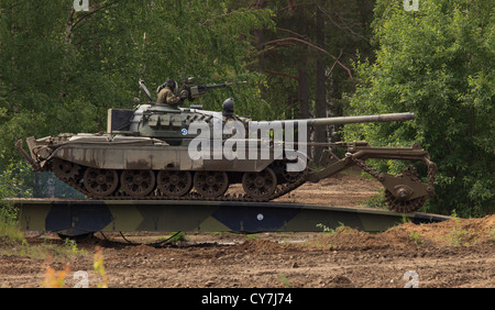 T-55M main battle tank of the Finnish Army with KMT-5 mine clearing roller crossing bridge. - Stock Photo