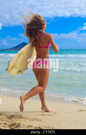 girl in pink bikini with surfboard running to the ocean - Stock Photo