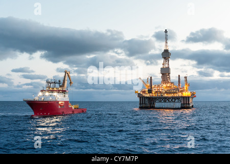 Oil rig with Supply boat in the north Sae - Stock Photo