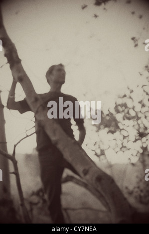 Blurred sepia toned silhouette of a man in the forest. - Stock Photo