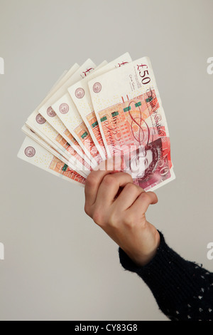 A yound girl holding a bunch of fifty pound notes in Brighton, East Sussex, UK. - Stock Photo